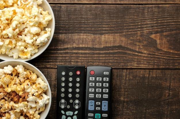 Pipoca e controle remoto de tv em uma mesa de madeira marrom, conceito de assistir filmes em casa, vista de cima