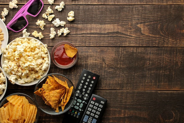 Pipoca e vários petiscos, óculos 3d, controle remoto de tv em um fundo de madeira marrom. conceito de assistir filmes em casa. vista de cima com espaço para texto