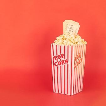 Pipoca em balde vermelho e branco com ingressos de cinema