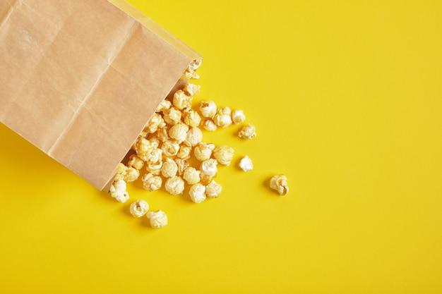 Pipoca em embalagem de papel em um espaço de cópia de fundo amarelo