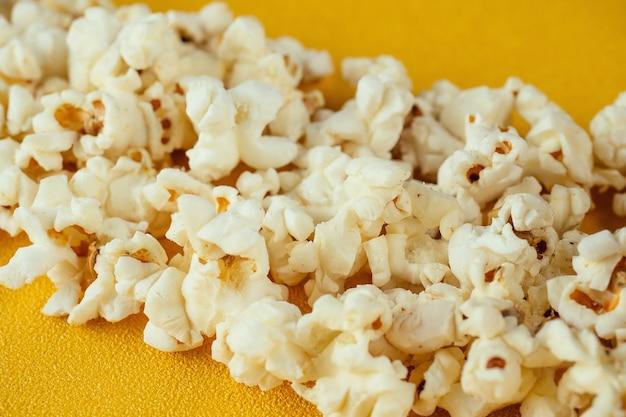 Pipoca em um fundo amarelo. o conceito de home cinema e filmes no cinema