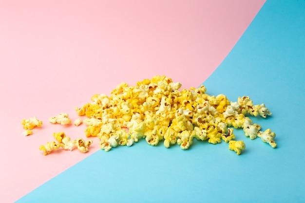 Pipoca em um fundo colorido. conceito de comida mínima. entretenimento, conteúdo de filme e vídeo. conceito de estética dos anos 80 e 90
