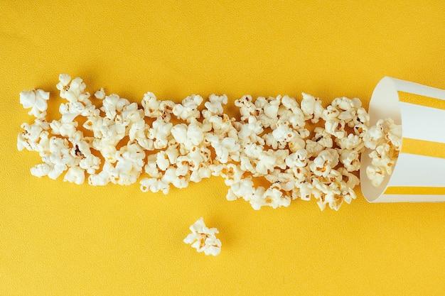 Pipoca espalhada de um copo de papel listrado. o conceito de home cinema e filmes no cinema.