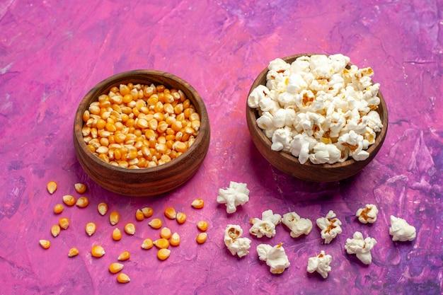 Pipoca fresca com grãos crus de frente no cinema de milho de mesa rosa