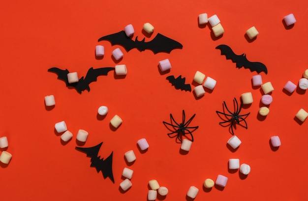 Pipoca, morcegos decorativos e aranhas em fundo laranja brilhante. composição de halloween