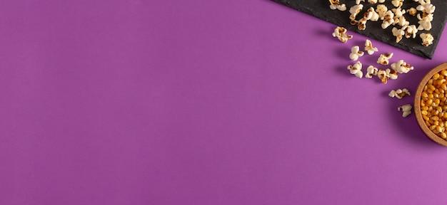 Pipoca na bandeja de ardósia e sementes de milho em fundo roxo. postura plana. copie o espaço. hora do filme caseiro.