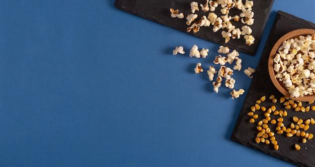Pipoca na bandeja de ardósia e sementes de milho sobre fundo azul. postura plana. copie o espaço. hora do filme caseiro.
