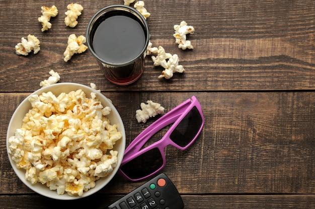 Pipoca, óculos 3d e controle remoto de tv em um fundo de madeira marrom. conceito de assistir filmes em casa. vista de cima