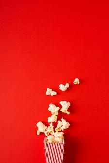 Pipoca plana leiga sobre fundo vermelho, com espaço de cópia