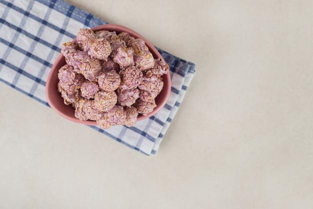 Pipoca roxa com sabor em uma tigela pequena sobre uma toalha cuidadosamente dobrada sobre mármore.