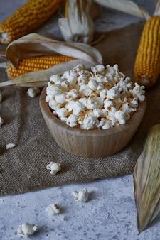 Pipoca tradicional em uma tigela de madeira e espigas de milho em cima da mesa.