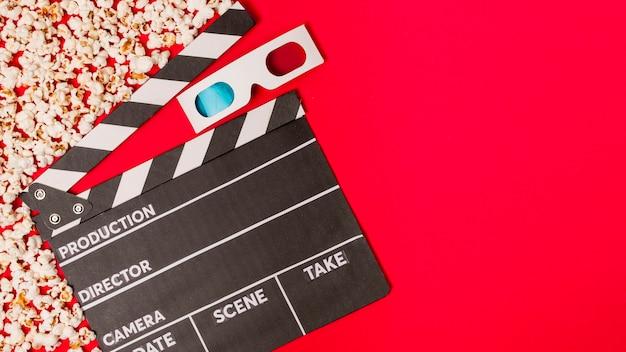 Pipocas com claquete e óculos 3d no pano de fundo vermelho