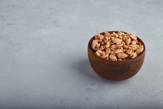 Pipocas de trigo em uma tigela de madeira com fundo de pedra.