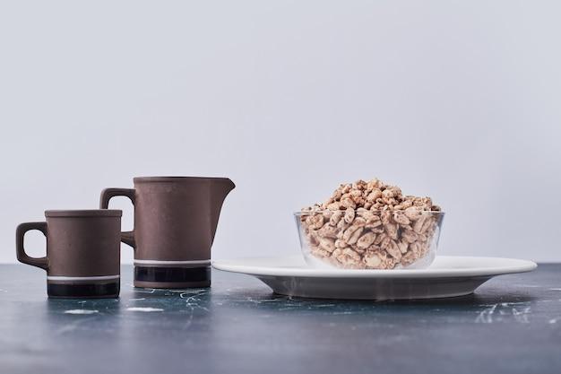Pipocas de trigo no copo de vidro em um prato branco com uma xícara e uma chaleira.