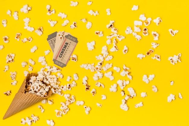 Pipocas derramadas do cone de waffle com ingresso de cinema