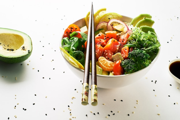 Pique a bacia com o molho dos salmões, do abacate e de soja isolado sobre o fundo branco. vista do topo