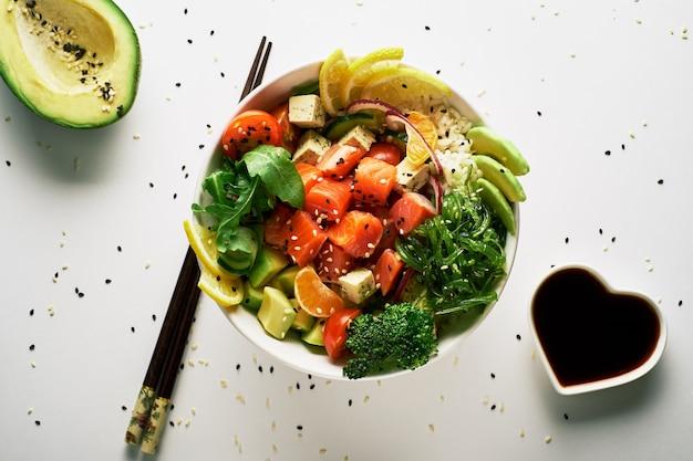 Pique a bacia com os brócolis salmon do arugula do pepino do abacate, com fundo do branco dos hashis. vista do topo