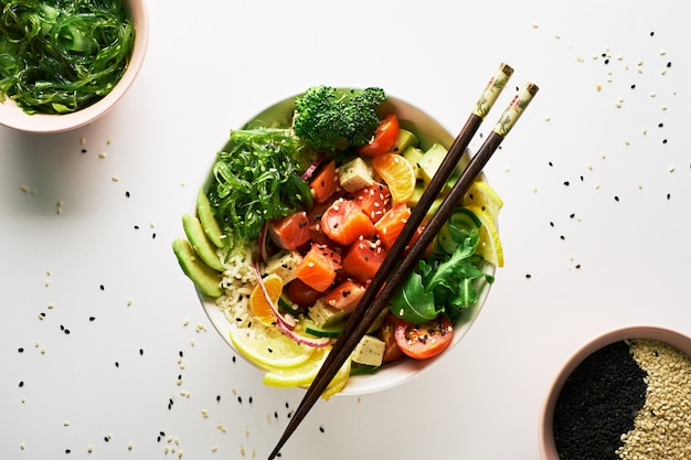 Pique a bacia com salmões, abacate, chopsticks isolados sobre o fundo branco. vista do topo