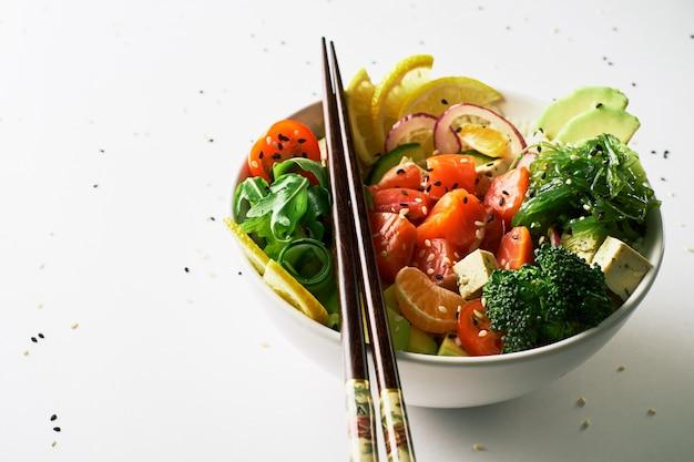 Pique a bacia com salmões, abacate, chopsticks isolados sobre o fundo branco. vista lateral
