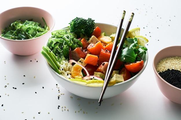 Pique a bacia com salmões, abacate, pepinos, rúcula, isolados sobre o fundo branco.