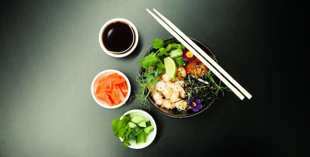 Pique a salada com camarão em uma tigela. ingredientes camarão, espinafre escaldado, tomate cereja, arroz, pepino, molho de soja e gengibre, molho picante, nori, gergelim, limão, coentro. conceito de salada de frutos do mar asiáticos.