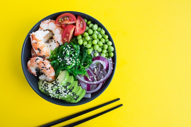 Pique a tigela com camarões vermelhos e legumes na tigela escura na superfície amarela.