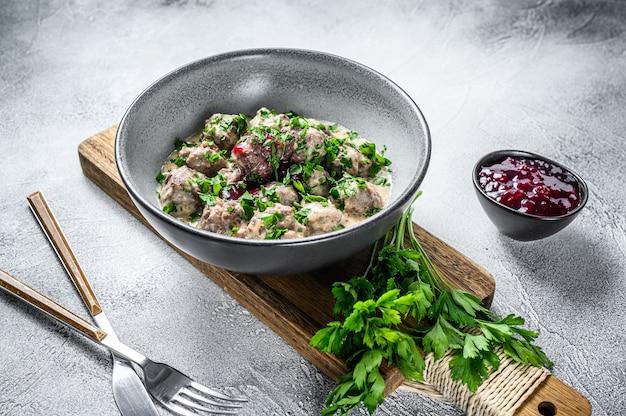Pique as almôndegas de carne com molho de natas num prato.