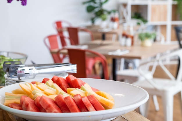 Pique os pedaços de melancia e abacaxi no prato branco o jantar e flor