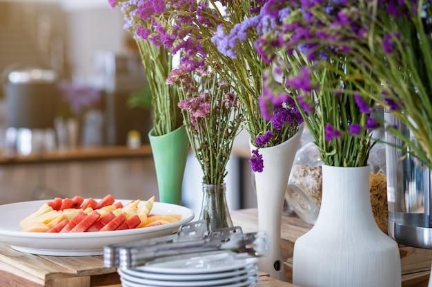 Pique os pedaços de melancia e abacaxi no prato branco o vaso de jantar e flor