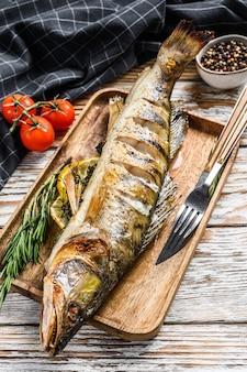 Piqueiro grelhado, peixe piqueiro. fundo de madeira branco. vista do topo.