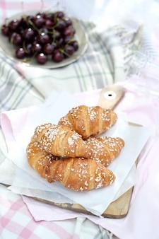 Piquenique ao ar livre com croissants e uvas