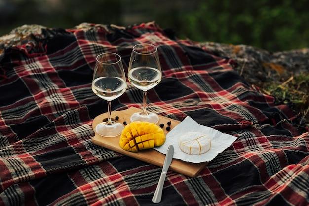 Piquenique com vinho branco, queijo brie e a deliciosa manga sobre uma colcha quadriculada sobre a natureza.