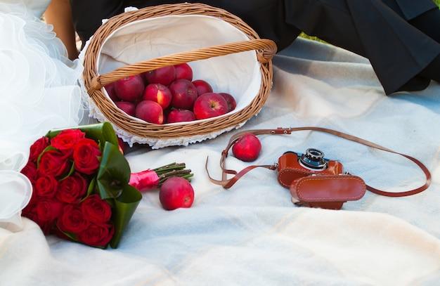 Piquenique de casamento com maçã, buquê de rosas e câmera velha