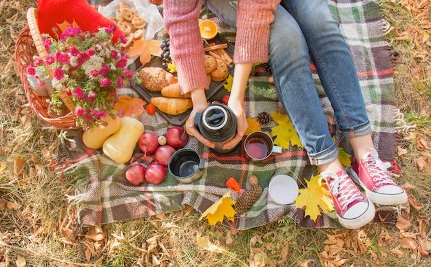 Piquenique de outono no parque, dia quente de outono. a garota tem uma garrafa térmica nas mãos com chá. cesta com flores, folhas de outono amarelas. conceito de outono.