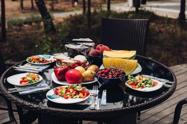 Piquenique de verão ao ar livre, salada servida nos pratos.