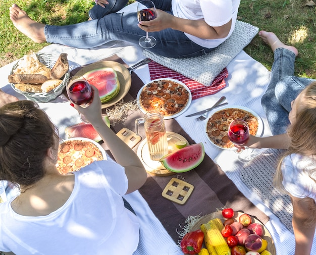 Piquenique de verão com amigos na natureza, com alimentos e bebidas.