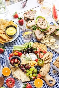 Piquenique de verão com tábua de queijos e sanduíches