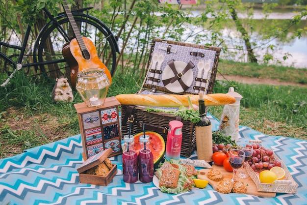 Piquenique de verão design close-up na natureza. na manta há uma cesta de comida.