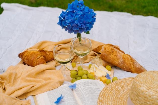 Piquenique de verão em dia ensolarado com pão, fruta, flores de hortênsia buquê, copos de vinho, chapéu de palha e livro.