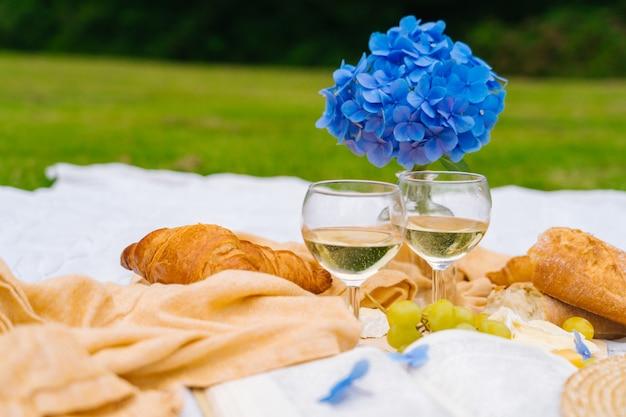Piquenique de verão em dia ensolarado com pão, frutas, buquê de flores de hortênsia, taças de vinho, chapéu de palha, livro e ukulele