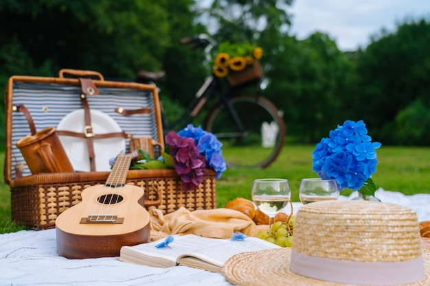 Piquenique de verão em dia ensolarado com pão, frutas, flores de hortênsia buquê, copos de vinho, chapéu de palha, livro e ukulele.