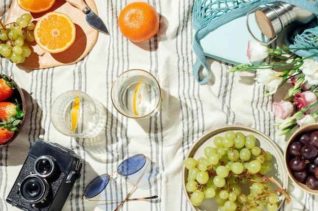 Piquenique de verão feminino flatlay, frutas, bagas e água de limão em cobertor de algodão listrado