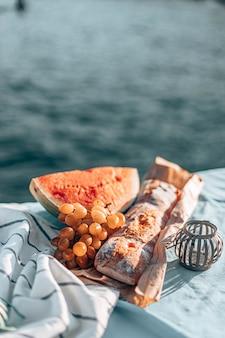 Piquenique de verão na praia. melancia fresca, baguete francesa e uvas em um cobertor.
