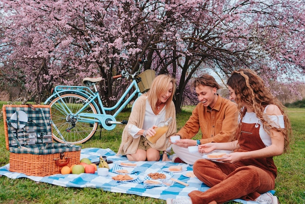 Piquenique em família. mãe com filho e filha, enquanto desfrutam de um dia ensolarado comendo alimentos saudáveis ao lado de uma cerejeira.
