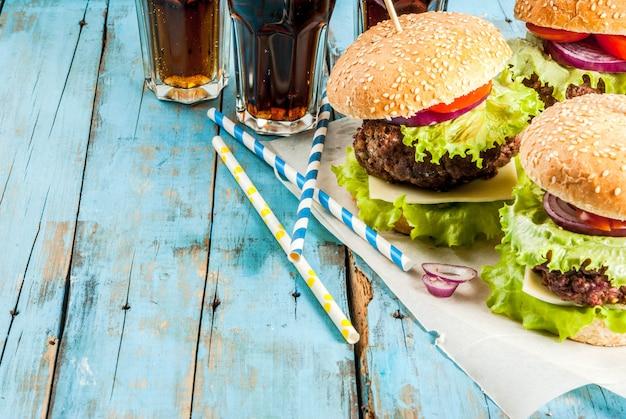 Piquenique, fast-food. alimentos não saudáveis. deliciosos hambúrgueres saborosos frescos com costeleta de carne, legumes frescos e queijo na velha mesa de madeira azul rústica com água com gás. copyspace