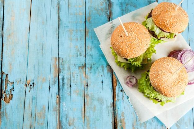 Piquenique, fast-food. alimentos não saudáveis. deliciosos hambúrgueres saborosos frescos com costeleta de carne, legumes frescos e queijo na velha mesa de madeira azul rústica com água com gás. vista do topo