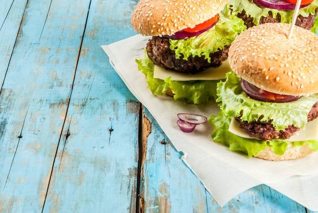 Piquenique fast food comida não saudável deliciosos hambúrgueres saborosos frescos com costeleta de carne legumes frescos e queijo na velha mesa de madeira rústica azul com água doce