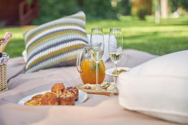 Piquenique gourmet com queijo de frutas frescas e vinho em volta de uma cesta de vime na grama verde de um parque