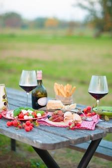 Piquenique italiano com vinho tinto, parmesão, presunto e azeitonas. almoço ao ar livre. petiscos tradicionais. copie o espaço