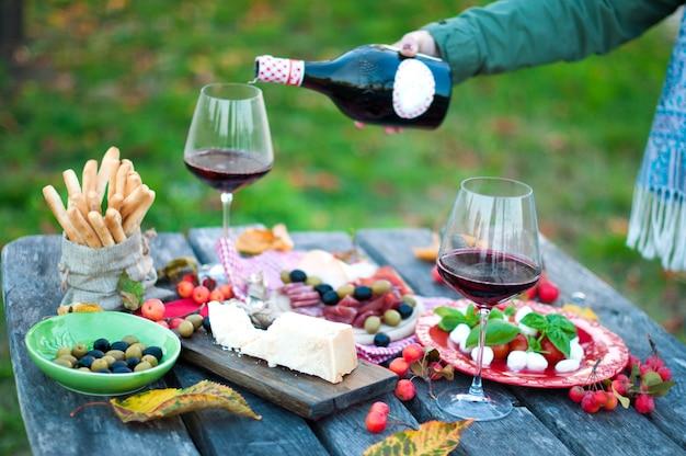 Piquenique italiano com vinho tinto, parmesão, presunto e azeitonas. almoço ao ar livre. petiscos tradicionais. um homem derrama um copo de vinho. copie o espaço